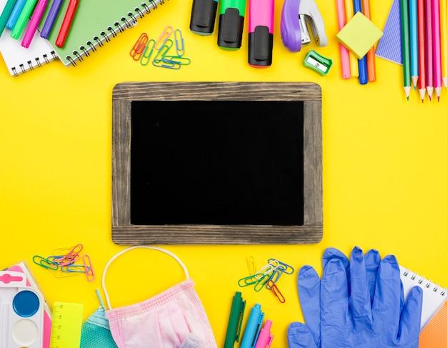 Disposizione piana degli elementi essenziali della scuola con guanti e matite colorate
