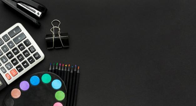 Disposizione piana degli elementi essenziali della scuola con il calcolatore e la cucitrice meccanica