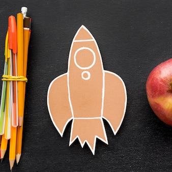 Disposizione piana degli elementi essenziali della scuola con la mela e le matite