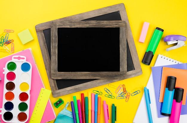 Disposizione piana degli elementi essenziali della scuola con lavagne e matite