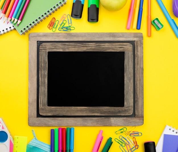 Disposizione piana degli elementi essenziali della scuola con le matite e la lavagna