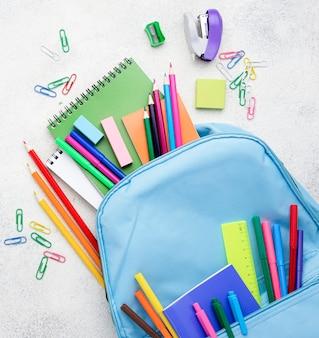 Disposizione piana degli elementi essenziali della scuola con le matite e lo zaino