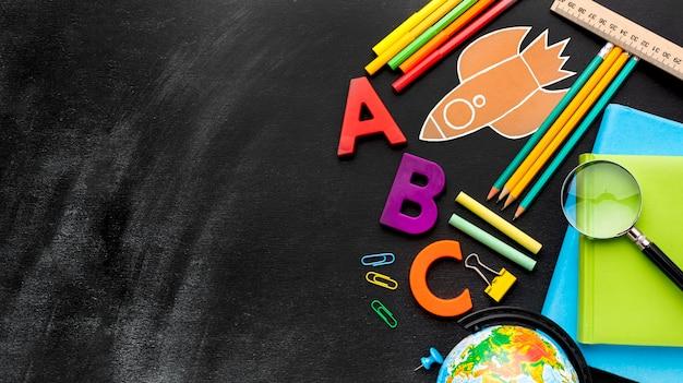 Disposizione piana degli elementi essenziali della scuola con lente d'ingrandimento e globo