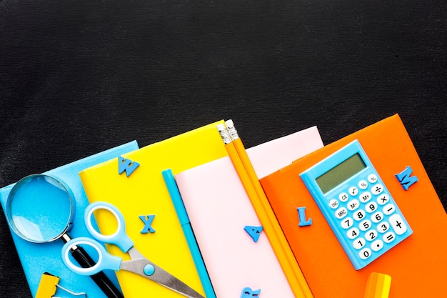 Disposizione piana degli elementi essenziali della scuola con libri e calcolatrice