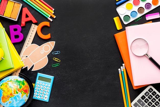 Disposizione piana degli elementi essenziali della scuola con libri e matite