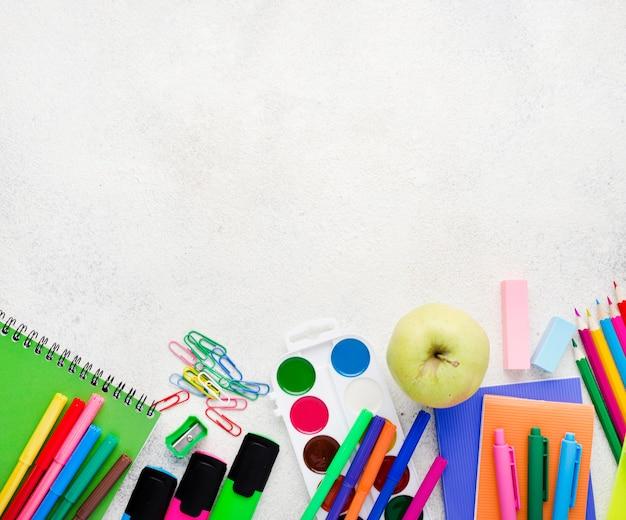 Disposizione piana degli elementi essenziali della scuola con matite e mela
