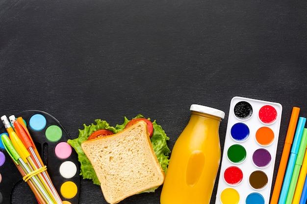 Disposizione piana degli elementi essenziali della scuola con sandwich e succo di frutta