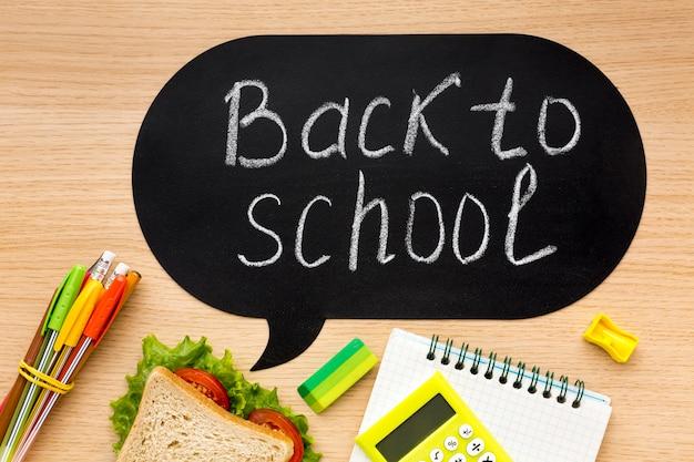 Disposizione piana degli elementi essenziali della scuola con sandwich e taccuino