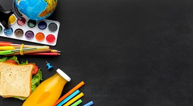 Disposizione piana degli elementi essenziali della scuola con succo e panino