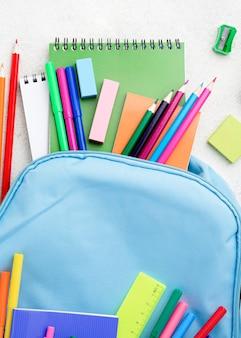 Disposizione piana degli elementi essenziali della scuola con zaino e matite