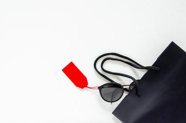 Disposizione piana degli occhiali da sole neri con i prezzi da pagare e il sacchetto della spesa rossi su fondo bianco per il concetto di vendita di black friday.