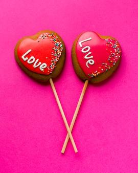 Disposizione piana dei biscotti a forma di cuore sul bastone e sul fondo rosa
