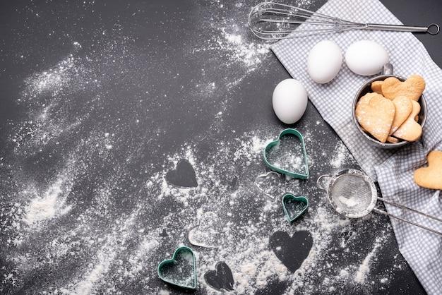 Disposizione piana dei biscotti di san valentino con lo spazio della copia e gli utensili della cucina