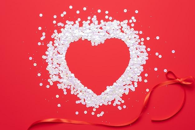 Disposizione piana dei coriandoli a forma di cuore di rosa pastello su fondo rosso