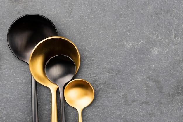 Disposizione piana dei cucchiai neri e dorati con lo spazio della copia