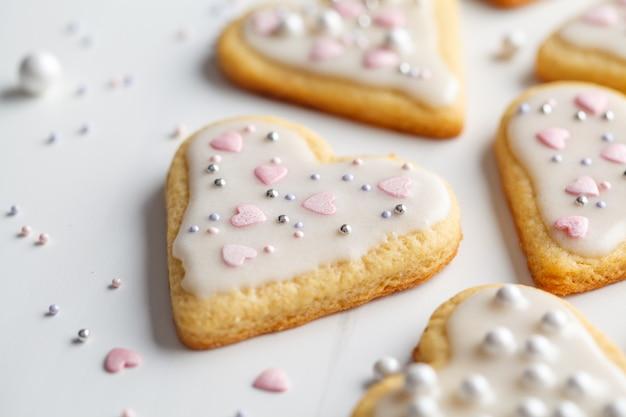Disposizione piana dei cuori dei biscotti con glassa e decorata per il san valentino, fondo bianco. concetto di san valentino.