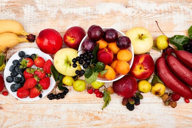 Disposizione piana dei frutti sopra fondo di legno bianco.