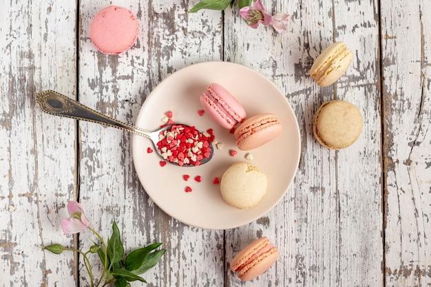 Disposizione piana dei macarons sul piatto con il cucchiaio e i fiori