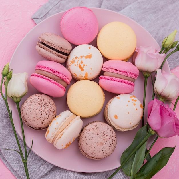 Disposizione piana dei macarons sul piatto con le rose