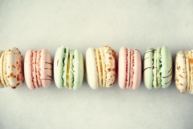 Disposizione piana dei maccheroni francesi variopinti. colori pastello macarons rosa, verde, giallo