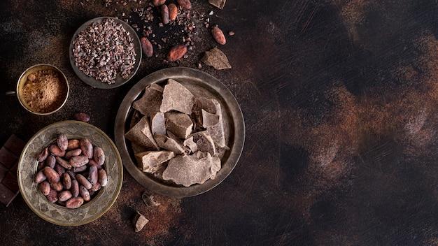 Disposizione piana dei pezzi di cioccolato sul piatto con fave di cacao e polvere e spazio della copia