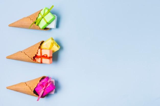 Disposizione piana dei regali variopinti in coni di gelato
