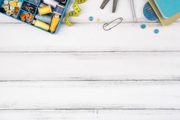 Disposizione piana dei rifornimenti di cucito sulla tavola di legno