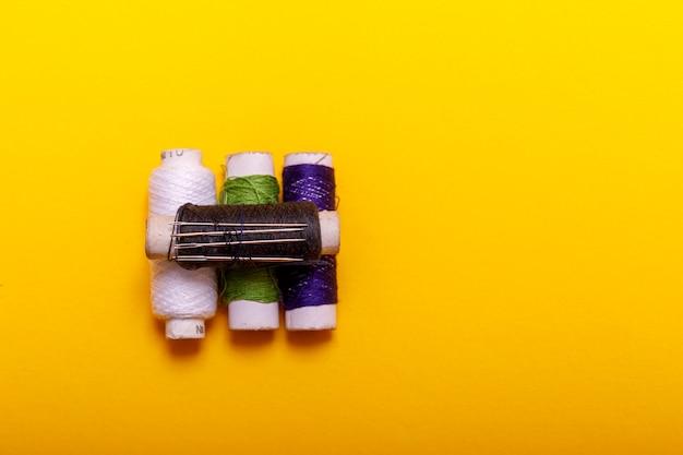 Disposizione piana dei rotoli e delle forbici colorati del filo per il cucito del fondo giallo. concetto di cucito e ricamo. strumenti per cucire e fatti a mano: filo, forbici.