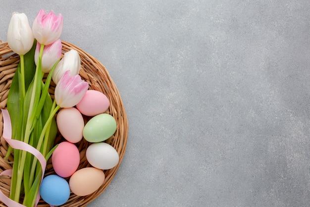 Disposizione piana dei tulipani multicolori con le uova di pasqua e lo spazio della copia