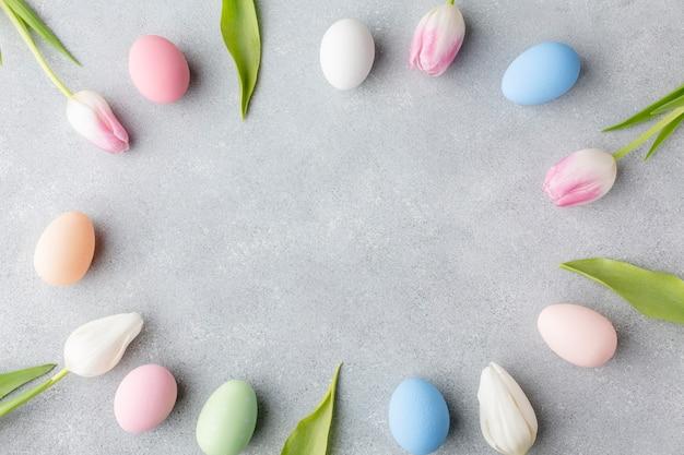 Disposizione piana dei tulipani variopinti e delle uova di pasqua