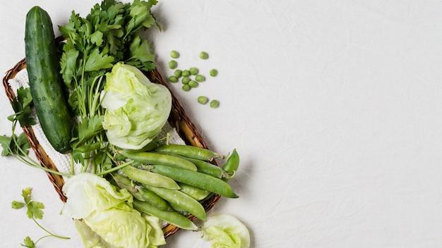 Disposizione piana del cetriolo e assortimento di merce nel carrello delle verdure