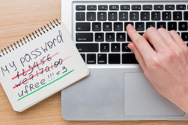 Disposizione piana del computer portatile con le mani e taccuino con informazioni sulla password