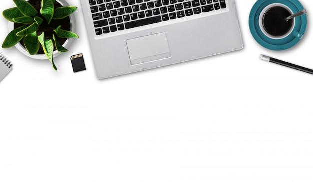Disposizione piana del computer portatile moderno, tazza di caffè, matita, blocco note, flash card, vaso da fiori con la pianta verde isolata sopra la parete bianca con lo spazio della copia. gadget moderno. luogo di lavoro dell'uomo d'affari