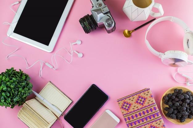 Disposizione piana del computer portatile, telefono cellulare, cuffie, aggeggio digitale, concetto moderno su fondo rosa molle