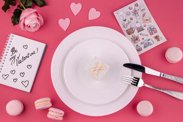 Disposizione piana del contenitore di regalo sul piatto con la rosa e i macarons