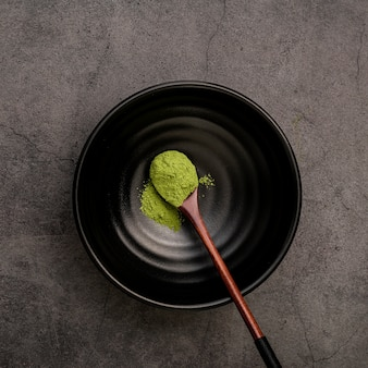 Disposizione piana del cucchiaio di legno in ciotola con la polvere del tè di matcha
