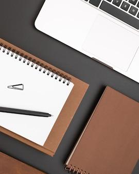 Disposizione piana del desktop con il taccuino in cima all'agenda e al computer portatile