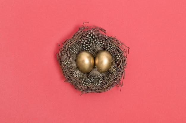 Disposizione piana del fondo rosa di corallo dorato delle uova di pasqua