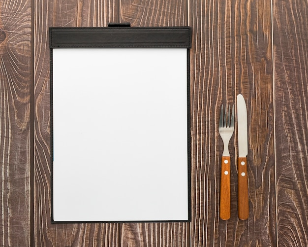 Disposizione piana del menu in bianco su superficie di legno con le posate
