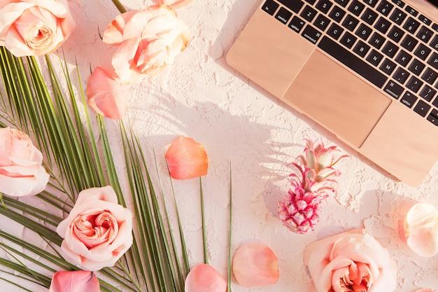 Disposizione piana del mockup di area di lavoro tropicale con laptop moderno, foglie di palma monstera, fiori rosa, ananas esotico e petali su pastello