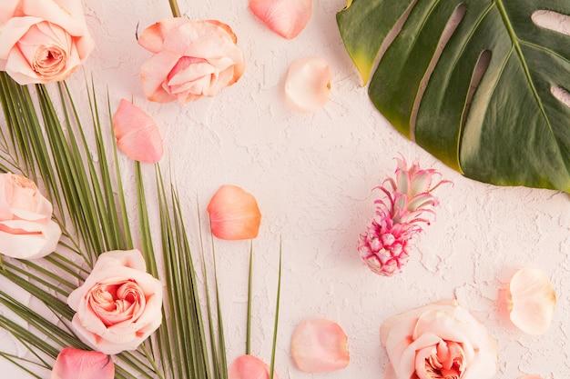 Disposizione piana del modello tropicale dell'area di lavoro con foglie di monstera di palma, fiori rosa, ananas e petali su pastello
