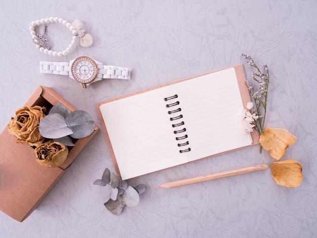 Disposizione piana del taccuino, dell'orologio e del braccialetto su fondo d'annata con lo spazio della copia