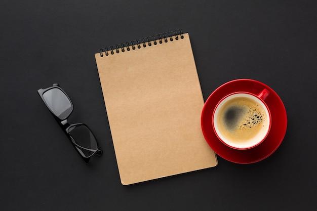 Disposizione piana del taccuino e della tazza di caffè sullo scrittorio del lavoro