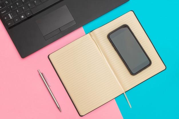 Disposizione piana dell'area di lavoro con laptop, notebook, smartphone e penna