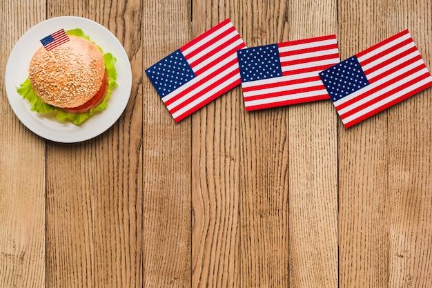 Disposizione piana dell'hamburger sul piatto con le bandiere americane su superficie di legno e spazio della copia