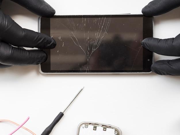 Disposizione piana dell'uomo che tiene telefono rotto