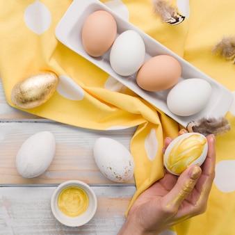 Disposizione piana dell'uovo dipinto per pasqua tenuta a mano