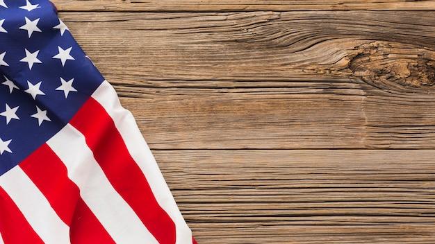 Disposizione piana della bandiera americana su superficie di legno con lo spazio della copia