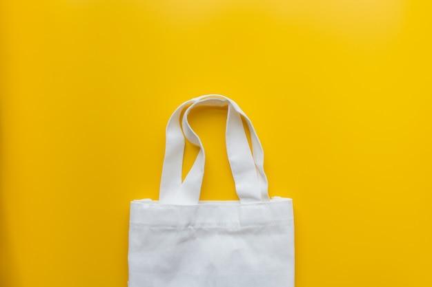 Disposizione piana della borsa di stoffa dei prodotti sostenibili su giallo