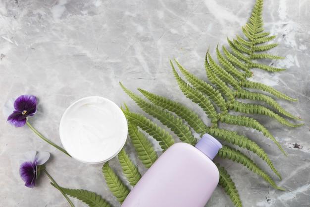 Disposizione piana della bottiglia e della crema per il corpo su fondo di marmo